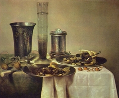 Still life with half-eaten pie, bier and silver cup on a table