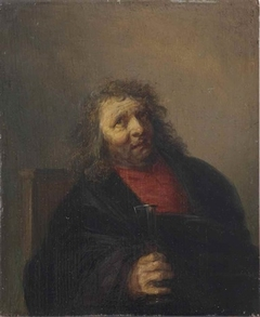 A bearded man seated in a chair drinking