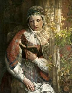 A woman in folk costume reading.