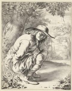 Een man doet hurkend zijn behoefte bij een boom