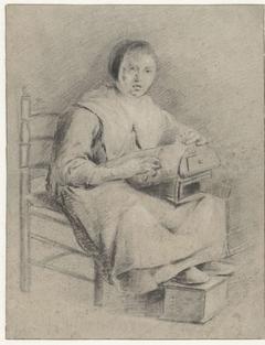 Zittende vrouw met kloskussen op schoot