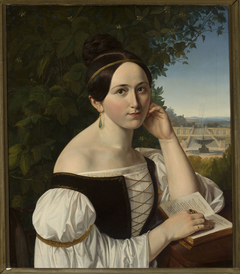 Portrait of a young woman with a book in a park