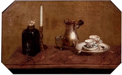 A silver coffee pot, cups on a tray, a bottle and a candlestick, on a tabletop