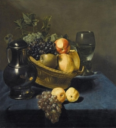 Still life with apples and grapes in a wicker basket on a table