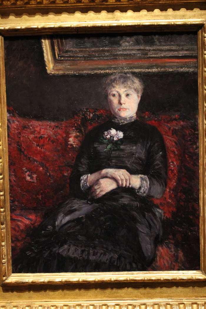 Woman Seated on a Red-Flowered Sofa