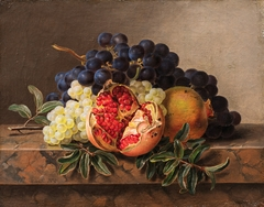 Pomegranates and green and blue grapes on a marble frame